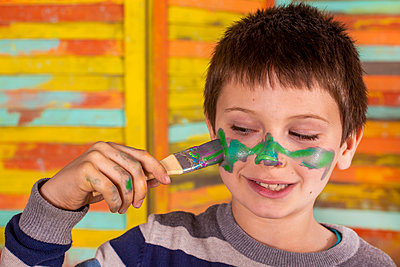 Boy painting his face with brush. - p1166m2165847 by Cavan Images