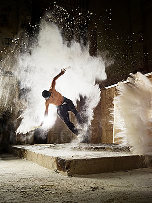 Man jumping in flour dust cloud during freerunning exercise - p300m2012472 von Christian Vorhofer