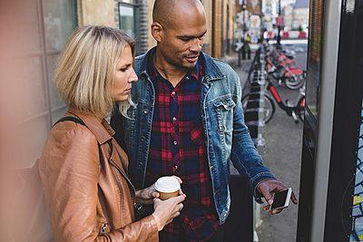 Multi-ethnic couple operating bike vending machine on sidewalk in city - p426m1442702 by Maskot