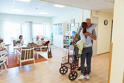Young woman embracing grandfather during visit at nursing home - p426m2072597 by Kentaroo Tryman