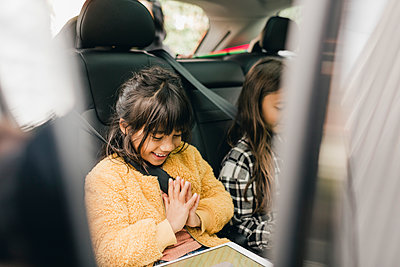Smiling girl using digital tablet while sitting in car - p426m2194947 by Maskot