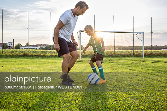 Coach and young football player on football ground at sunset - p300m1581381 von Fotoagentur WESTEND61