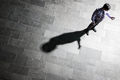 View from above of a businessman checking his phone and his shadow on the lobby floor. - p1100m1554072 by Mint Images