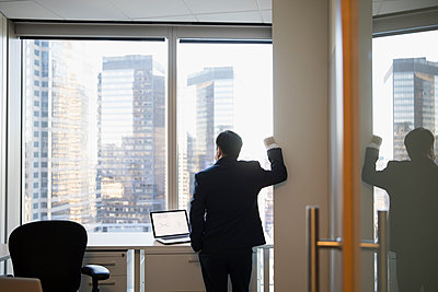 Pensive businessman looking out office windows at highrise buildings - p1192m1231112 by Hero Images