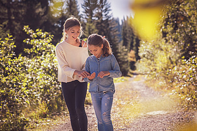 Two sisters walking on forest path - p300m2166381 by Studio 27