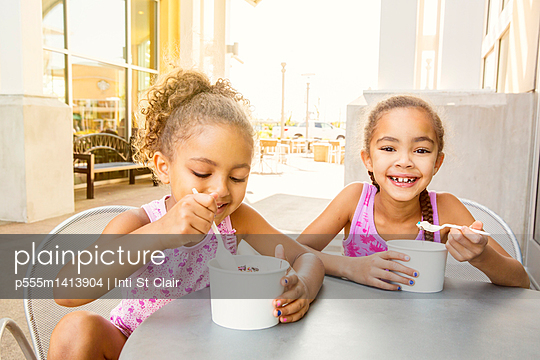 Mixed race sisters eating ice cream at outdoor cafe - p555m1413904 by Inti St Clair photography