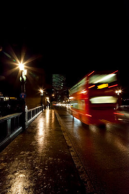 A Red double decker bus travelling towards a bridge at night - p1302m1196092 by Richard Nixon