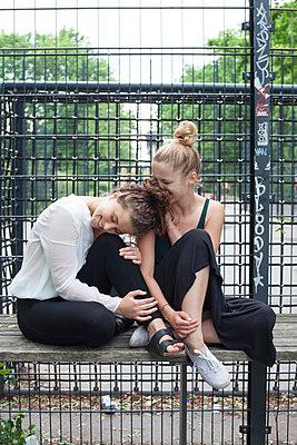 Zwei junge Frauen sitzen vor einem Sportplatz - p1303m1143524 von Ansgar Schwarz