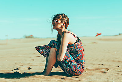 Young woman sitting in desert landscape - p300m2004289 by Oriol Castelló Arroyo