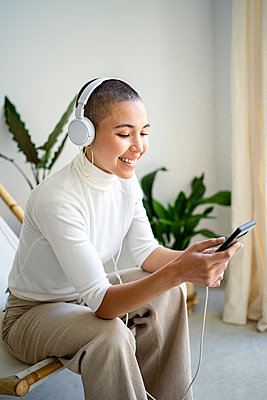 Smiling woman using smart phone at home - p300m2256533 by Rafa Cortés