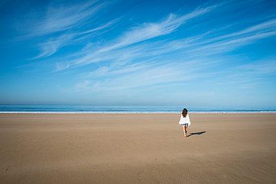 Caucasian woman walking on beach under blue sky - p555m1412389 by Alberto Guglielmi