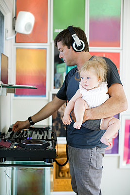 Mid adult man cooking, listening to headphones and carrying baby daughter - p924m1422856 by Sasha Gulish