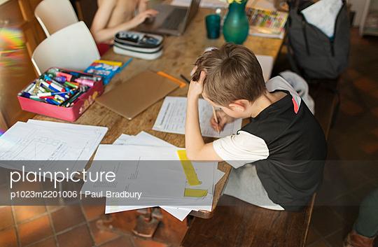 Boy homeschooling at dining table - p1023m2201006 by Paul Bradbury