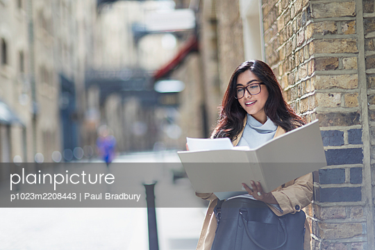 Businesswoman reviewing paperwork on sunny city street - p1023m2208443 by Paul Bradbury