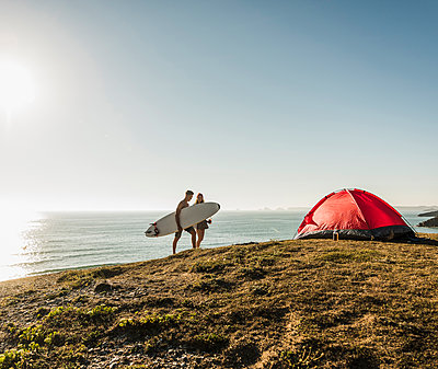 Young couple with surfboard camping at seaside - p300m1189290 by Uwe Umstätter
