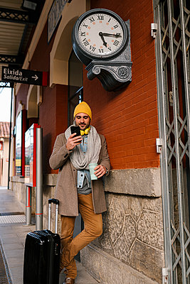 Fashionable man using mobile phone while standing with luggage on station - p300m2251683 by Ezequiel Giménez