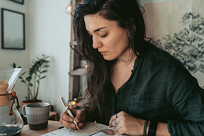 Woman making notes in diary - p312m2191298 by Rania Rönntoft
