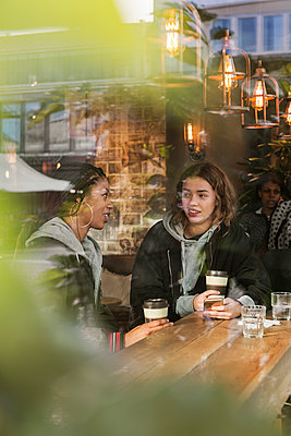 Teenage girls in cafe - p352m2121086 by Folio Images