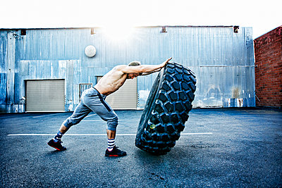 Caucasian man working out with heavy tire outdoors - p555m1304124 by Peathegee Inc