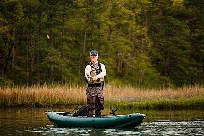 Caucasian man fishing on kayak - p555m1503979 by Roberto Westbrook