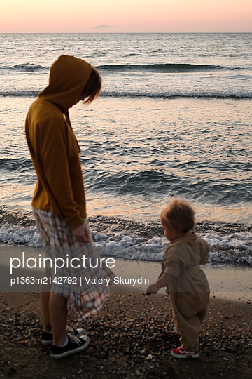 Woman with baby playing on beach  - p1363m2142792 by Valery Skurydin