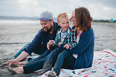 Happy family sitting at beach during sunset - p1166m1210265 by Cavan Images