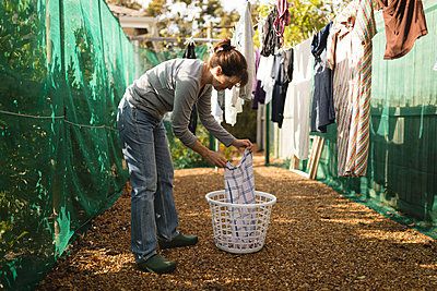 Senior woman hanging laundry on clothes line on a sunny day - p1315m1518613 by Wavebreak