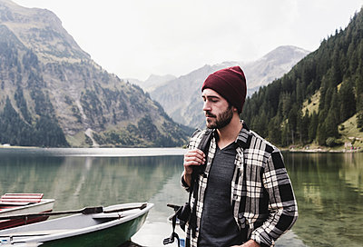 Austria, Tyrol, Alps, serious man at mountain lake - p300m1505629 by Uwe Umstätter