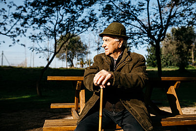 Spain, Barcelona. Retired senior man sitting on park bench leaning on his cane - p300m2166541 von Josep Rovirosa