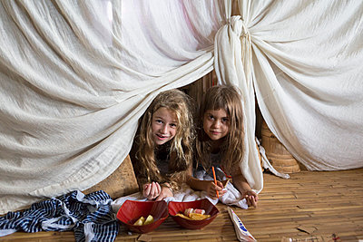 Caucasian girls playing in blanket fort - p555m1419644 by Marc Romanelli