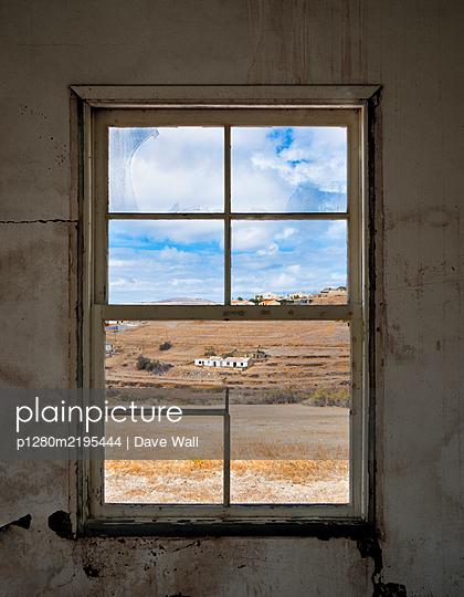 Blick durch ein zerbrochenes Fenster auf Landschaft - p1280m2195444 von Dave Wall
