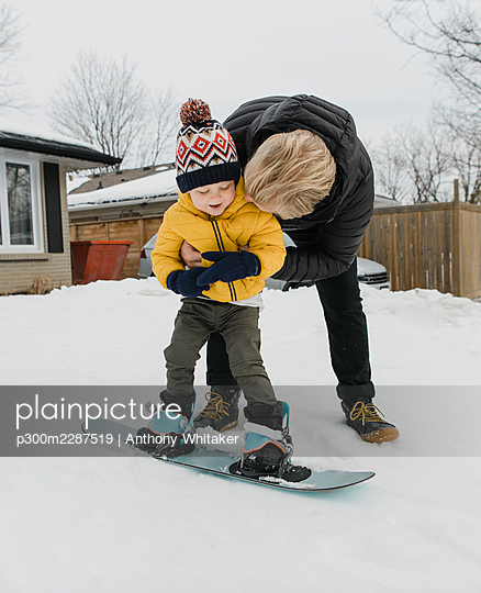 Loving father embracing son learning snowboarding during winter - p300m2287519 by Anthony Whitaker