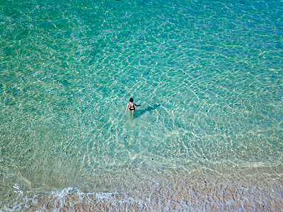 Indonesia, Bali, Melasti, Aerial view of Karma Kandara beach, woman going into water - p300m2042558 by Konstantin Trubavin