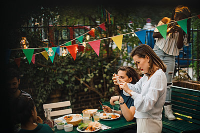 Young woman photographing through mobile phone during dinner party - p426m2046211 by Maskot