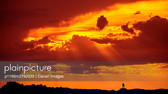 Silhouette of Man Standing In Desert Landscape Under Incredible Sunset - p1166m2192039 by Cavan Images