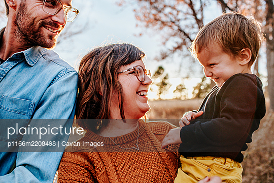 Parents smiling and laughing at young child on a fall evening - p1166m2208498 by Cavan Images