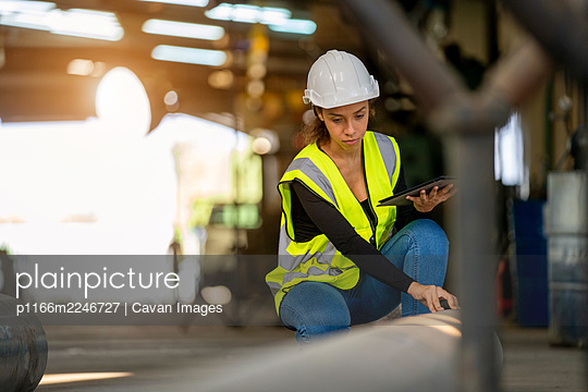 Young female in protective uniform inspecting industrial machine - p1166m2246727 by Cavan Images