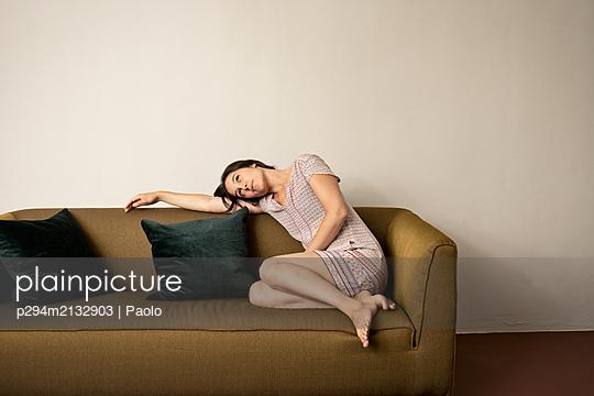Brünette Frau chillt auf dem Sofa - p294m2132903 von Paolo