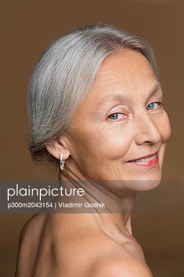 Portrait of naked senior woman with grey hair in front of brown background - p300m2043154 von Vladimir Godnik