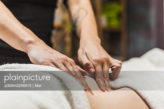 Hands of female chiropractor massaging back of young woman - p300m2256915 by Mar