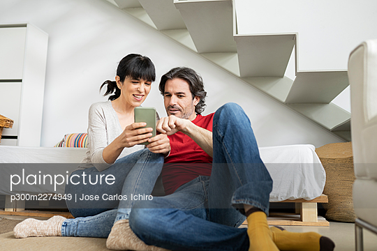 Couple discussing over smart phone while sitting at home - p300m2274949 by Jose Carlos Ichiro