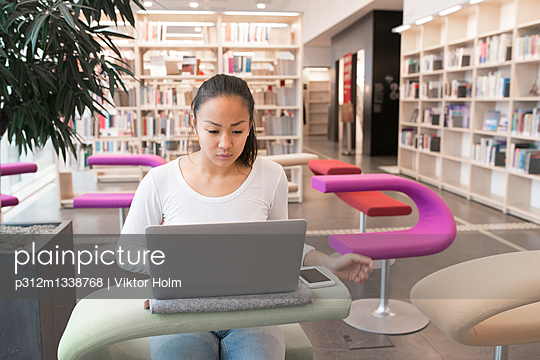 Young woman using laptop in library - p312m1338768 by Viktor Holm