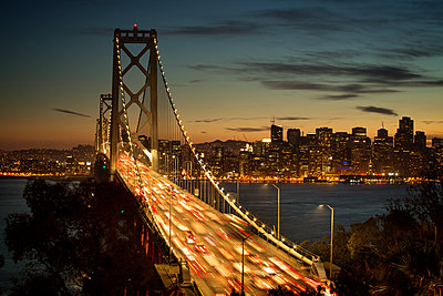 Blurred motion of vehicles on Oakland Bay Bridge at night - p1166m1144753 by Cavan Images