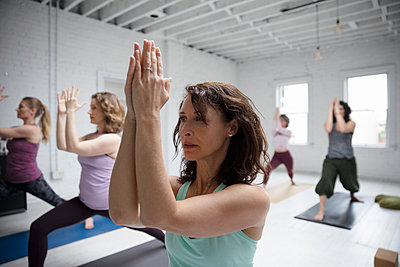 Focused woman practicing yoga warrior one pose in yoga class - p1192m1583395 by Hero Images
