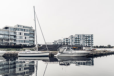 Modern buildings near harbor with moored boats against sky - p300m2240081 by Christophe Papke