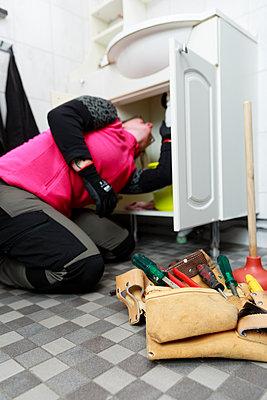 Female plumber repairing bathroom sink - p312m2262878 by Phia Bergdahl