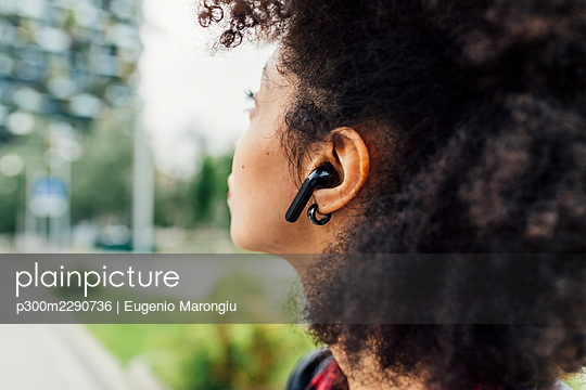 Young woman listening music through wireless in-ear headphones - p300m2290736 by Eugenio Marongiu