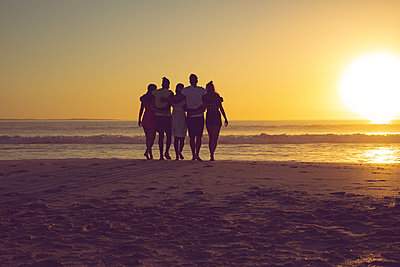 Friends with arms around walking towards the beach during sunset - p1315m2117912 by Wavebreak