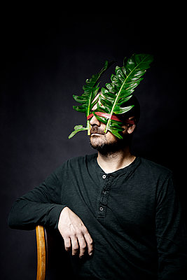 Man with big leaves on the face - p1521m2150078 by Charlotte Zobel