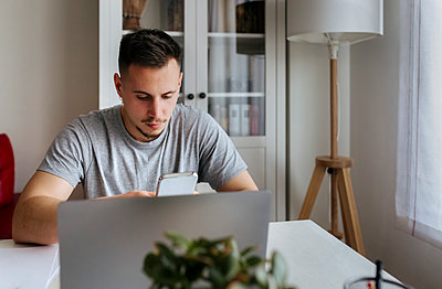 Young male entrepreneur using smart phone while sitting with laptop at home office - p300m2267745 by Marco Govel